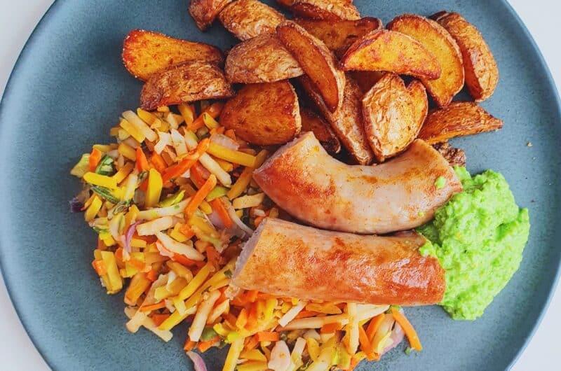 Medister i ovn på bund af kartofler og grøntsager