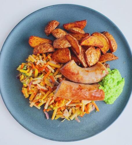 Ovnbagt medister på grøntsagsbund med kartoffelbåde og ærtedip